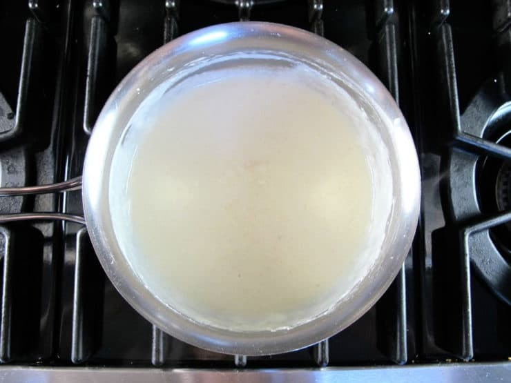 Milk added to a roux in a saucepan.
