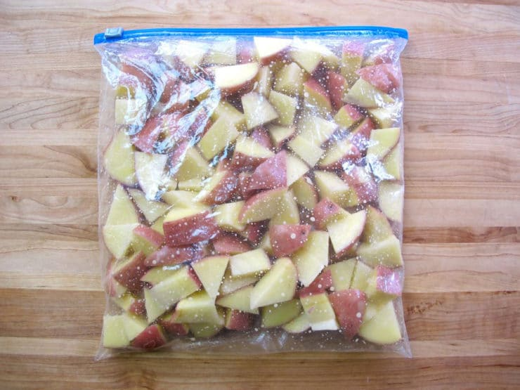 Potatoes and oil in a zipper top bag.