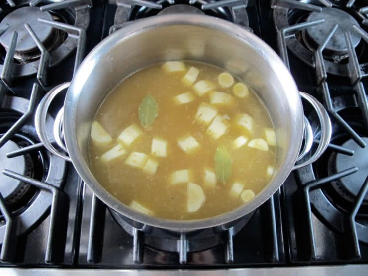 Chopped potatoes in broth in a stockpot.