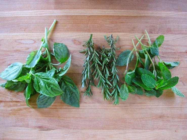 Bunches of rinsed herbs on a cutting board.