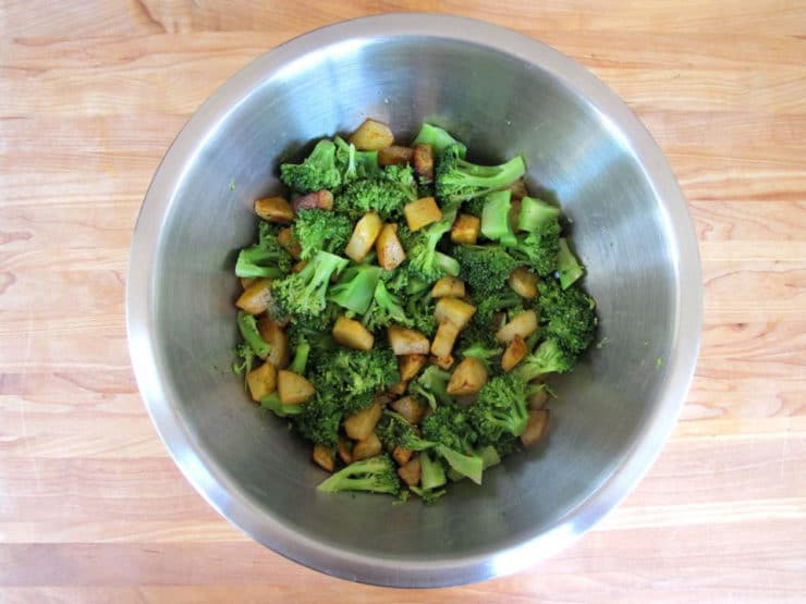 Cooked broccoli and potatoes in a mixing bowl.