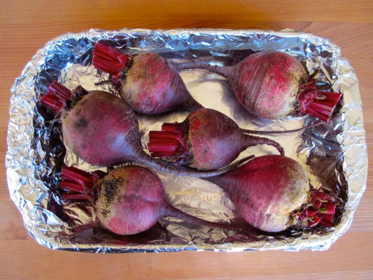 Cleaned beets in a foil lined baking dish.