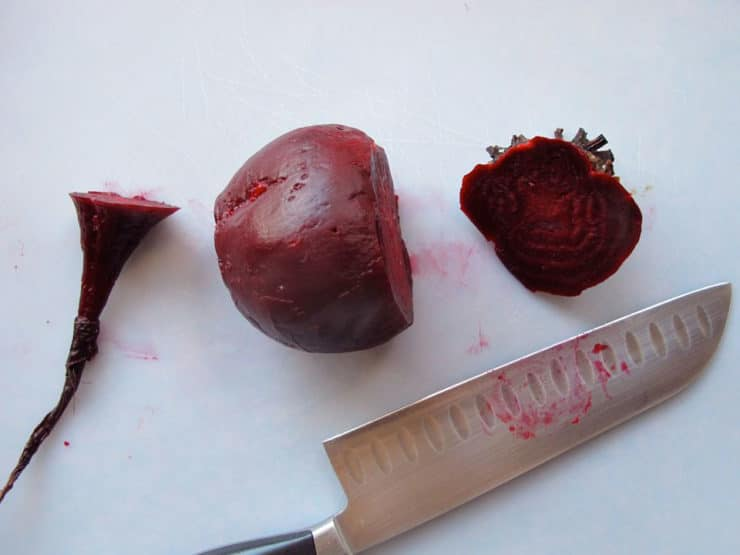 Slicing the tops and bottoms off roasted beets.