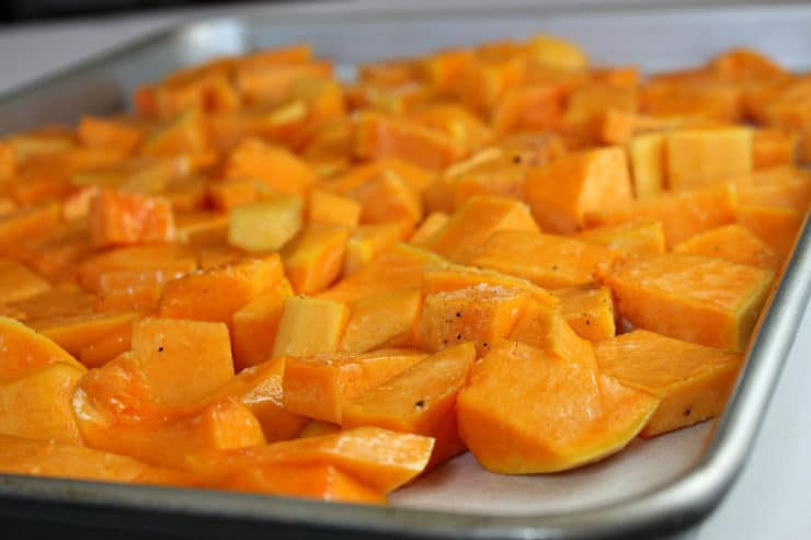 Roasted, diced butternut squash on a baking sheet.