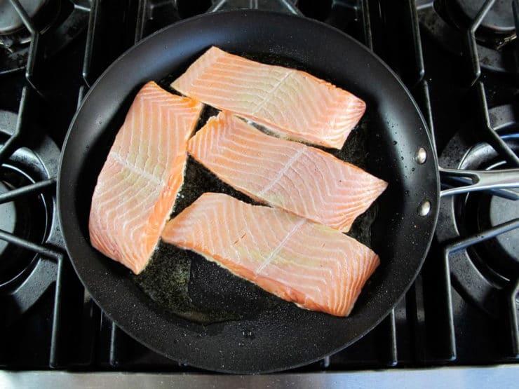 Salmon fillets in a skillet.