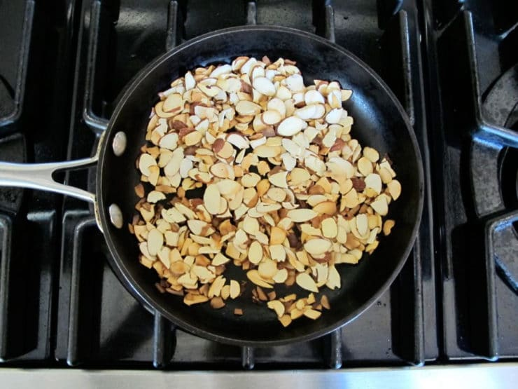Toasting sliced almonds in a skillet.