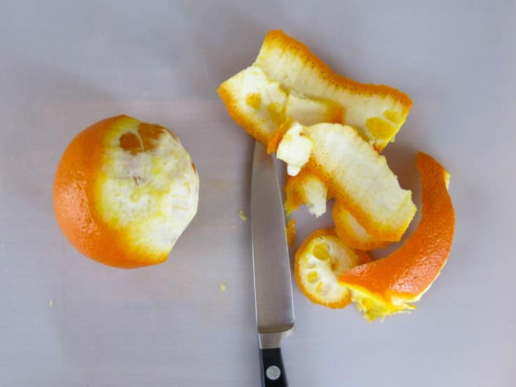 Slicing peel and pith off an orange.