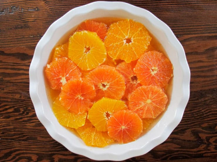Sliced oranges soaking in simple syrup.