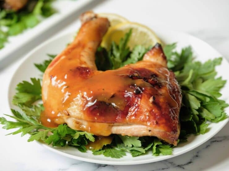 Horizontal shot - whole roast chicken leg topped with honey garlic sauce on a bed of parsley garnish on white plate, platter of chicken in background, on a marble countertop.
