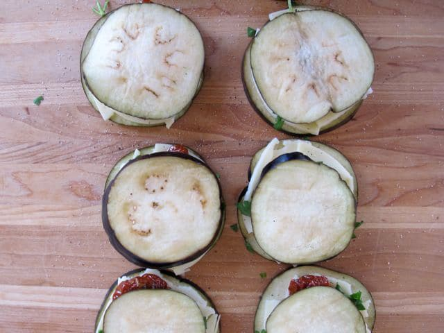 Stacking layers of eggplant rounds.