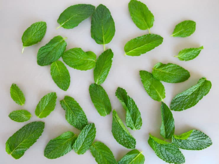 Rinsed mint leaves spread out on a cutting board.