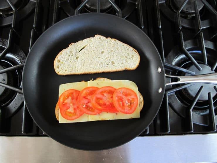 Tomato slices on sourdough bread in a skillet.