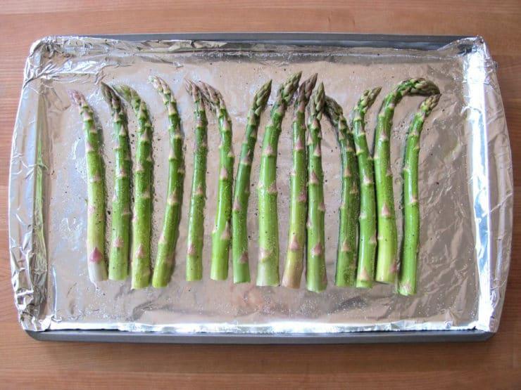 Asparagus stalks on a foil-lined baking sheet.