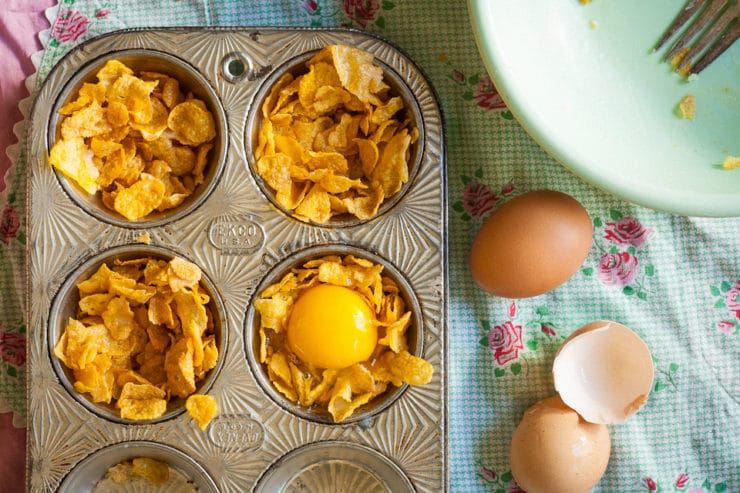 Breaking eggs into cornflake nests in a muffin tin.