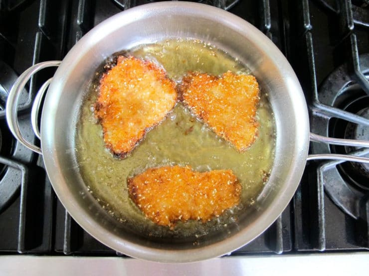Coated fish fillets frying in a skillet.