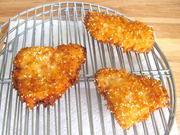 Fried fish fillets draining on a rack.