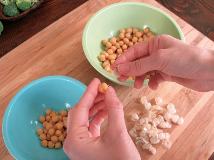 Popping chickpeas out of their skins.