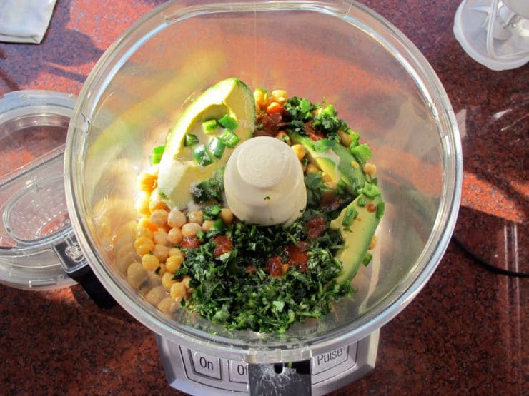 Chickpeas and other ingredients in a food processor.