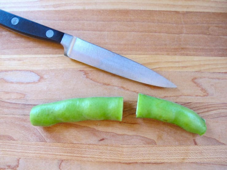 Slicing fava bean pod in half.