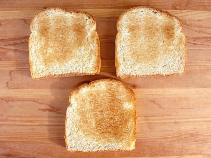 Three slices of toast on a cutting board.