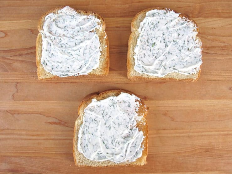 Herbed cream cheese spread on three slices of toast.