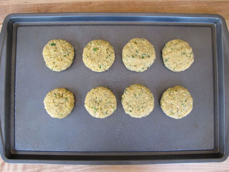 Chickpea patties on a baking sheet.