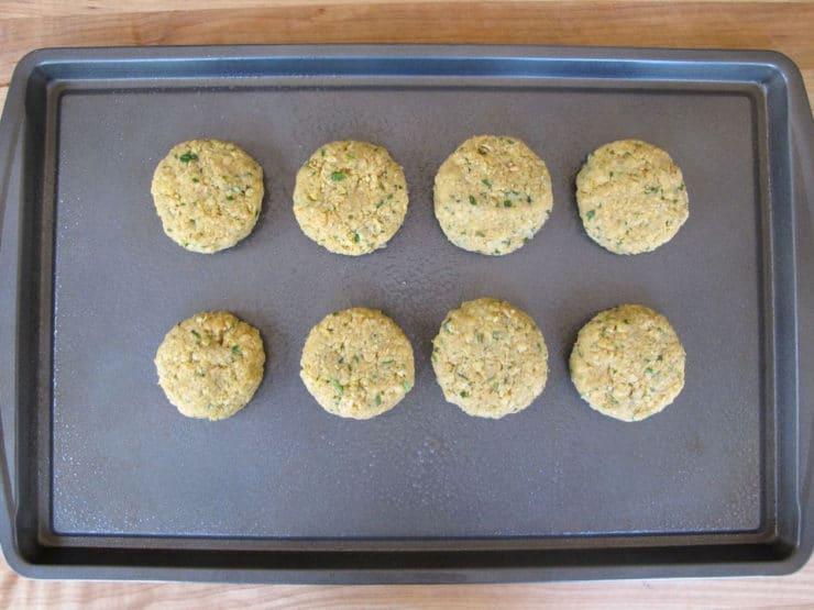 Chickpea patties on a baking sheet.