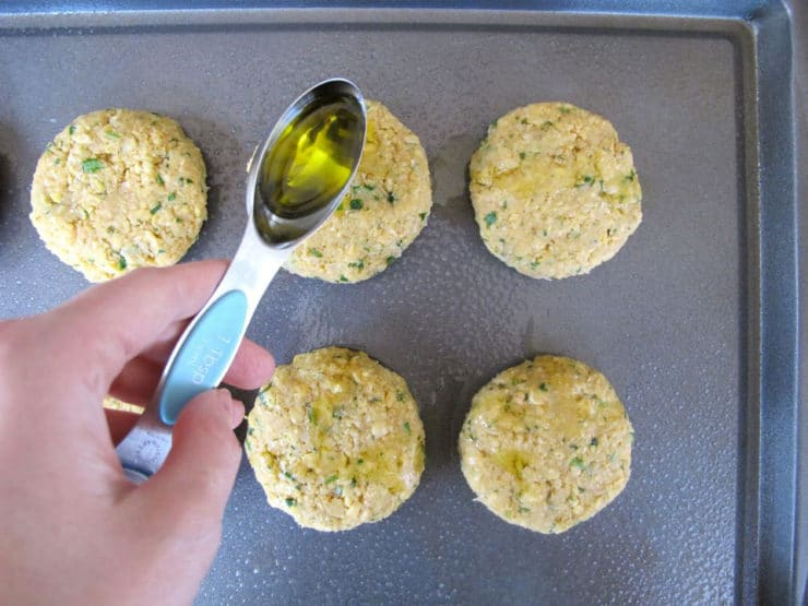 Drizzling oil over chickpea patties on a baking sheet.