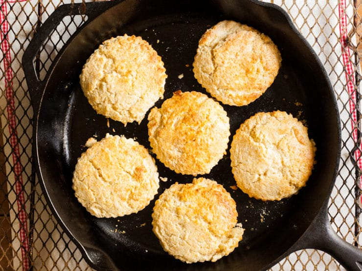 Biscuits cooking in a cast iron skillet.