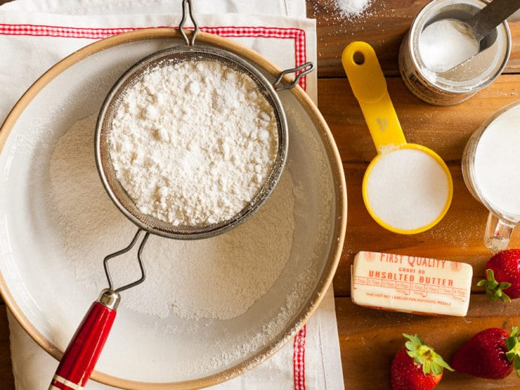 Sifting flour into a mixing bowl.