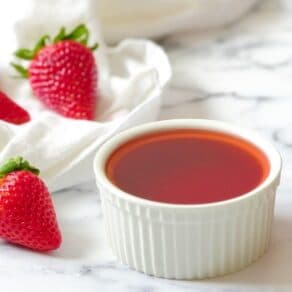 Square Crop - Strawberry Simple Syrup in a white dish on a white marble background with fresh strawberries.