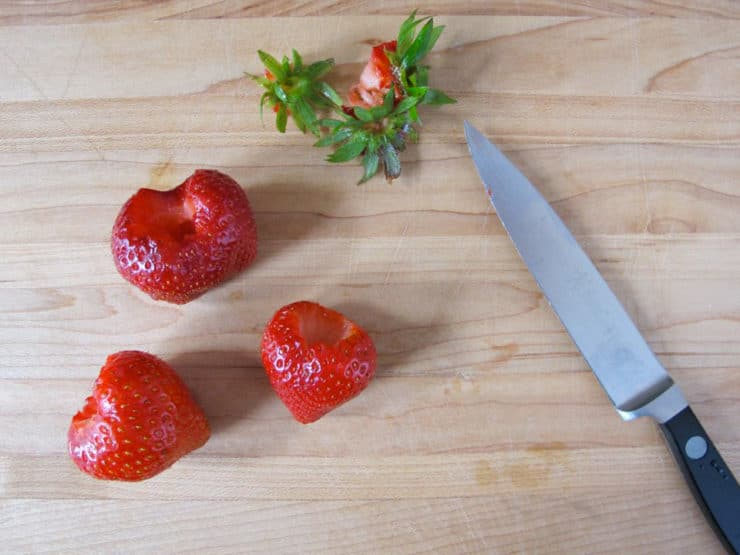 Hulled strawberries on a cutting board.