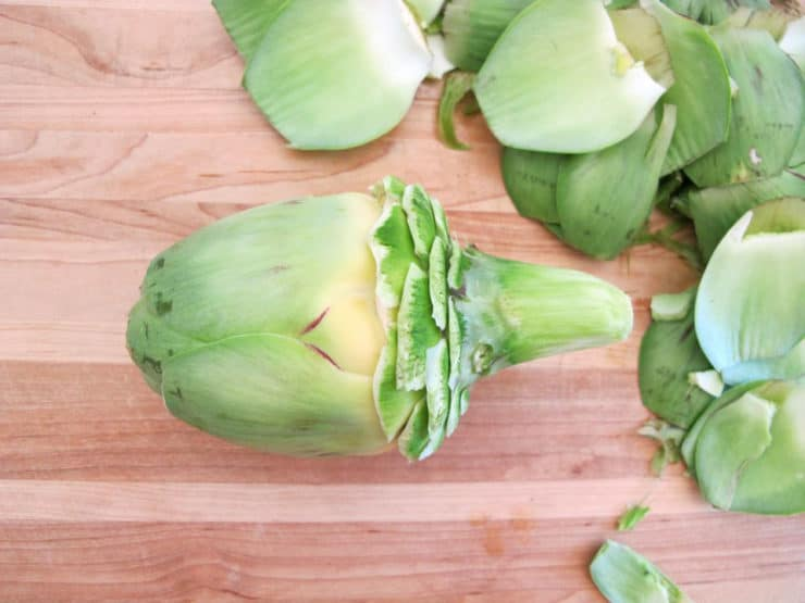Peeling outer leaves from an artichoke.