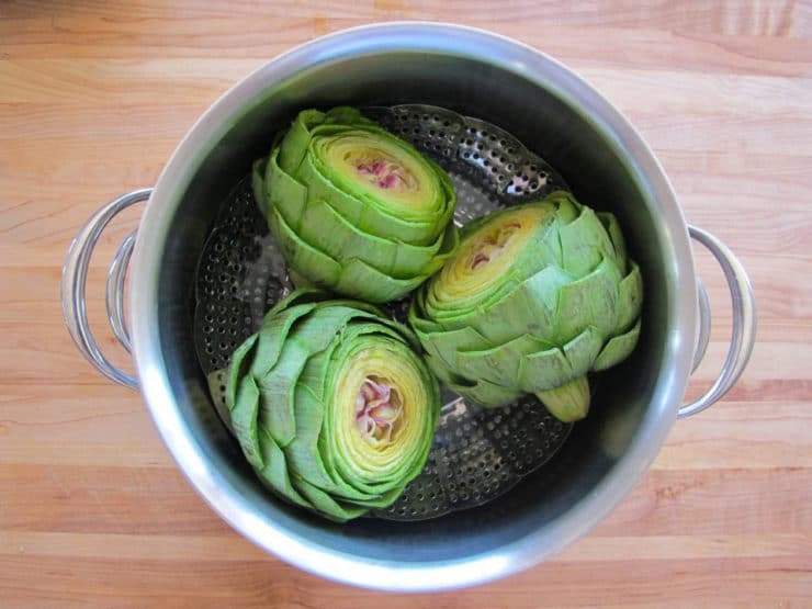 Artichokes in a steamer basket.