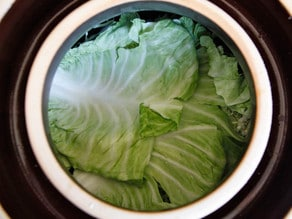 Fermentation crock overhead shot - top layer of whole cabbage leaves.