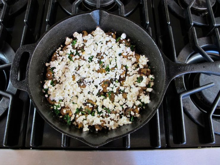 Goat cheese sprinkled over mushrooms in a skillet.