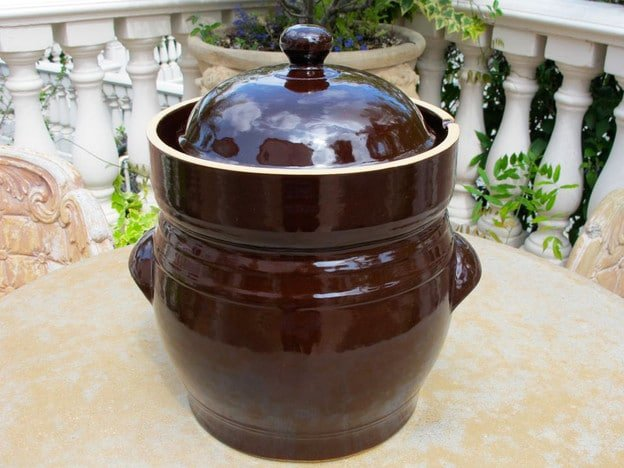 Brown ceramic fermentation crock on outdoor table.