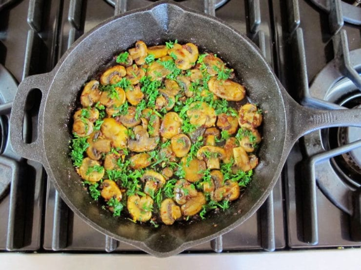 Herbs spread over sauteed mushrooms in a skillet.