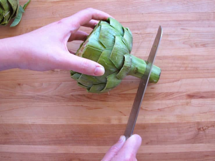 Slicing off an artichoke stem.