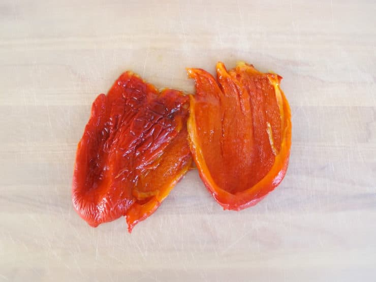 Roasted red peppers on a cutting board.
