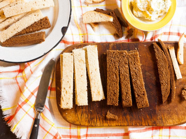 Rye bread on a cutting board sliced into long fingers.