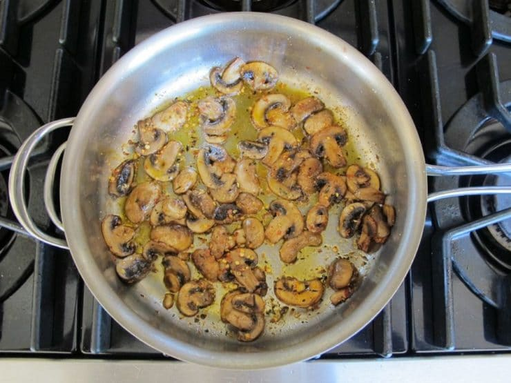Sliced mushrooms frying in a saucepan.
