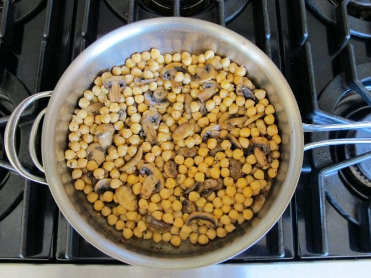 Chickpeas added to mushrooms in a saucepan.