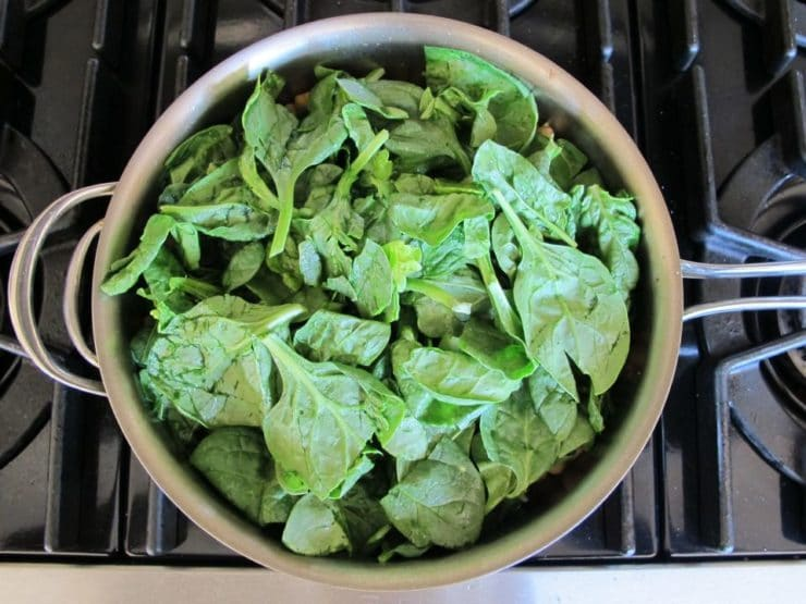 Spinach and kale added to a saucepan.