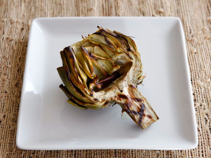 How to Grill Artichokes - Give your artichokes a smoky flavor by finishing them on the grill. Learn how to clean, prep, steam, grill and sauce for tender, smoky results.