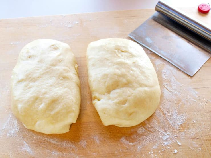 Ball of dough divided in half on a cutting board.
