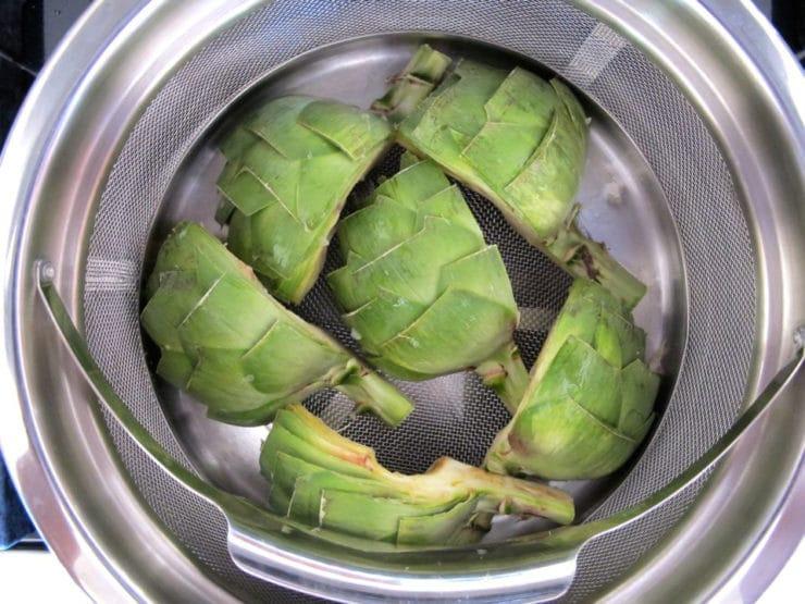 Steaming artichoke halves in a pot.