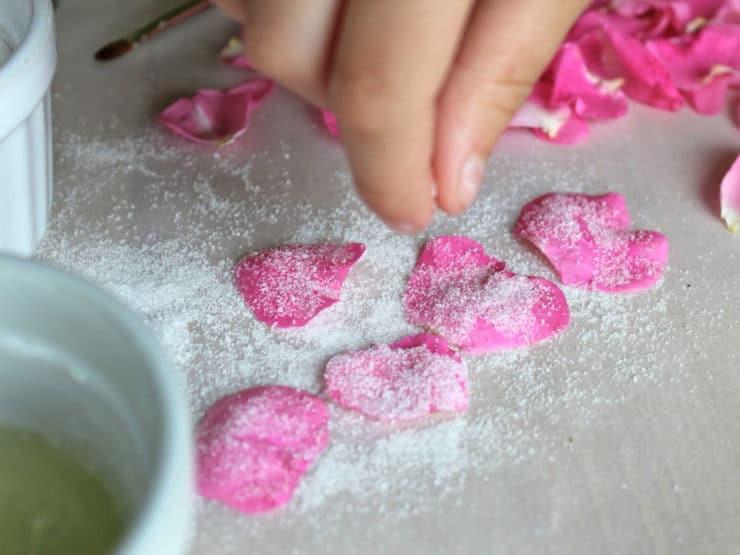 Sprinkling sugar over rose petals.