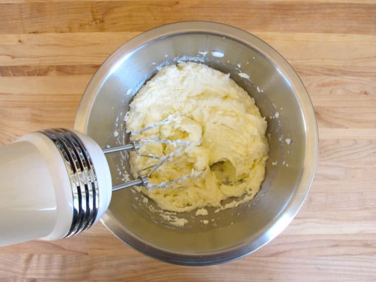 Creaming butter and sugar with a hand mixer.