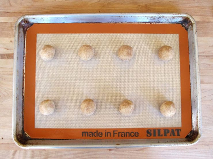 Cookie dough balls on a lined baking sheet.